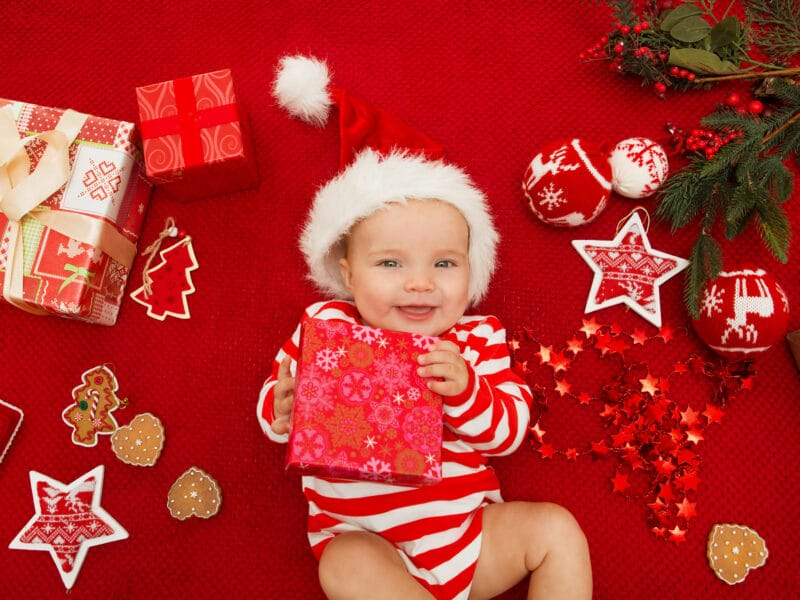 Baby in striped onesie with santa hat holding present
