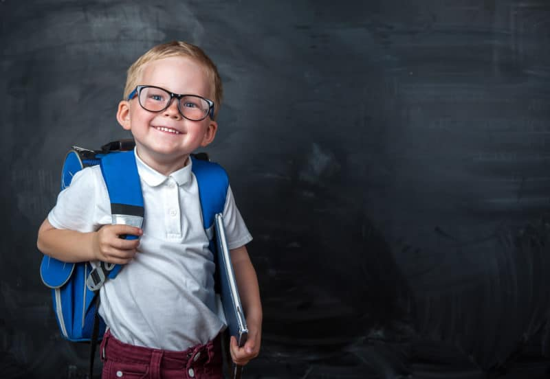 Little boy with glasses holding a backpack in front of a chalkboard.