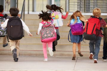 Kids with backpacks running into school