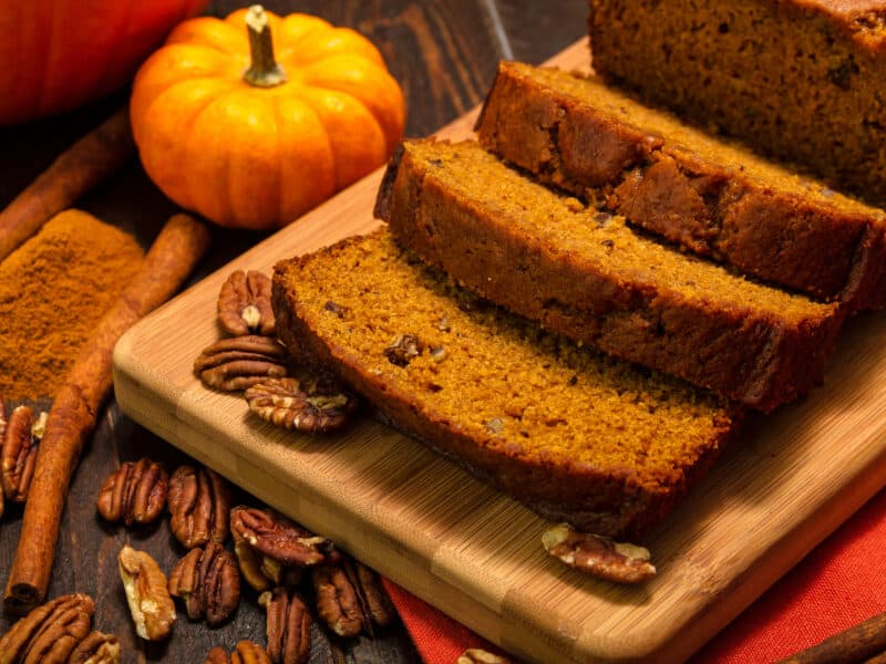 Pumpkin nut bread made with pecans on a cutting board with extra sprinkling of pecans next to a small pumpkin