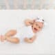 smiling baby in crib laying on her back