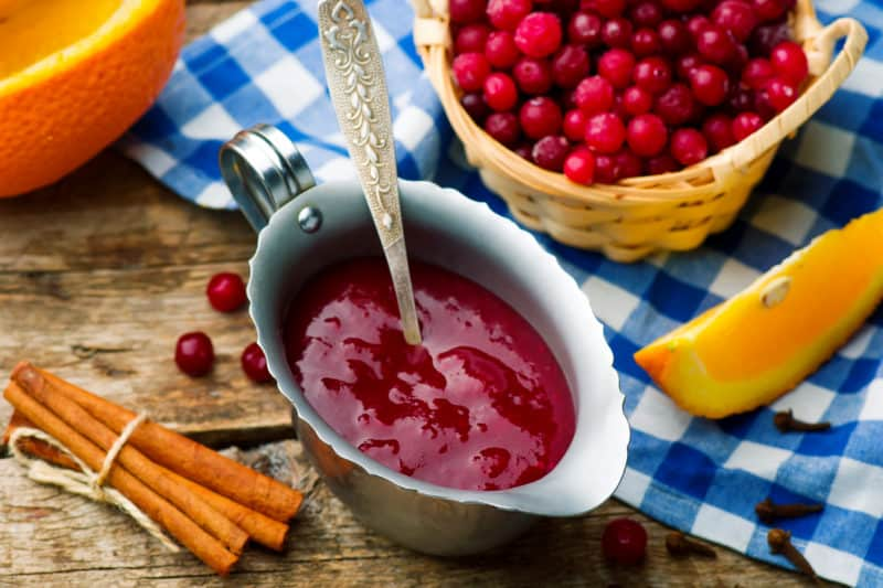Cranberry Sauce in a serving bowl next to a bowl full of fresh cranberries