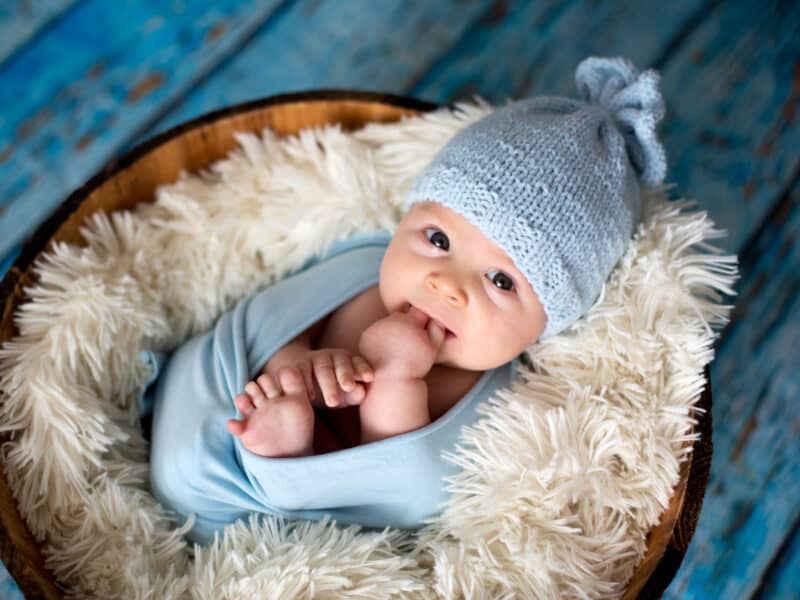 baby swaddled in a blue blanket with a blue cap resting in a basket