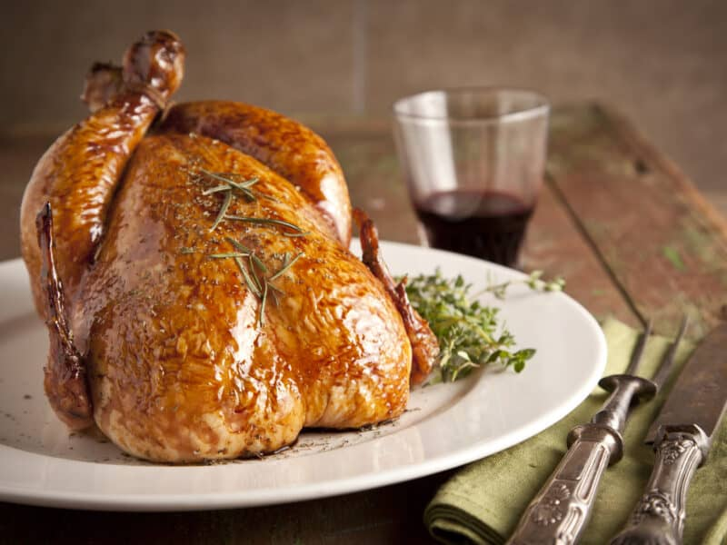 A whole Herbed Roasted Turkey on a plate ready to be served